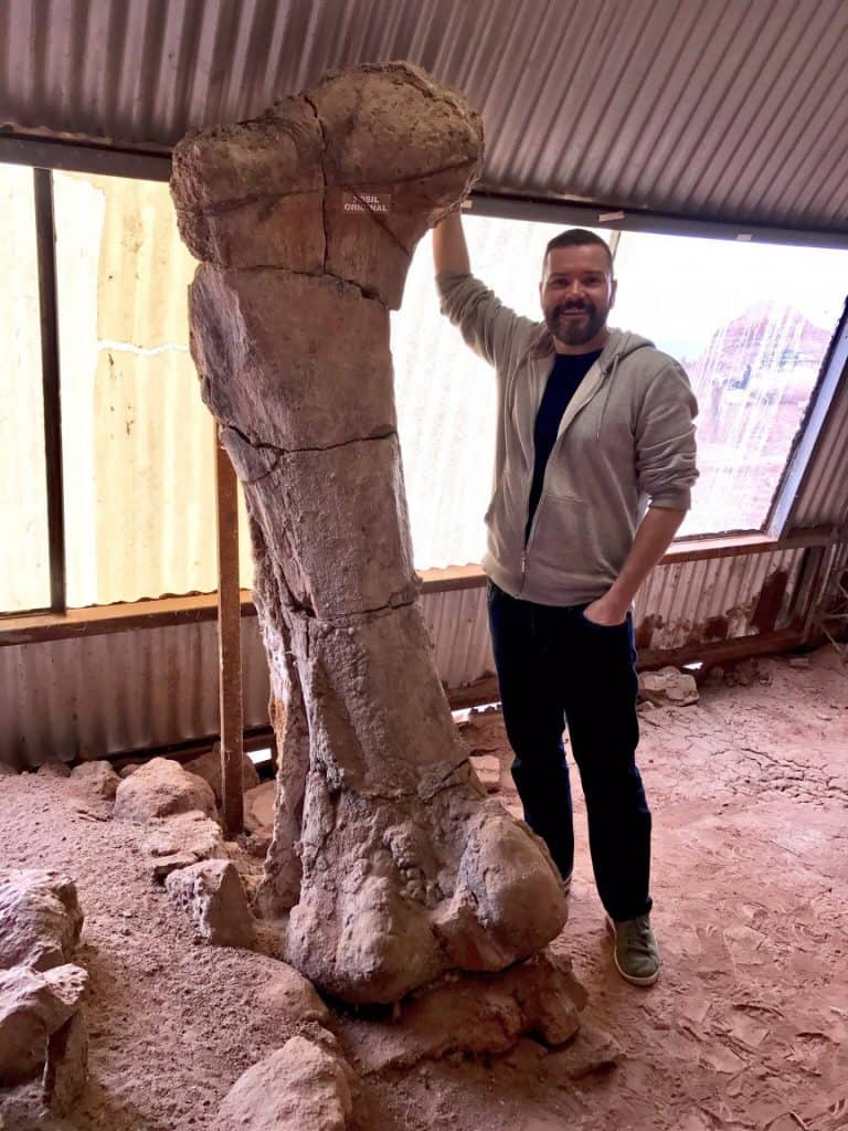 John Pickrell with the femur of thigh bone of a massive sauropod called Futalongkosaurus