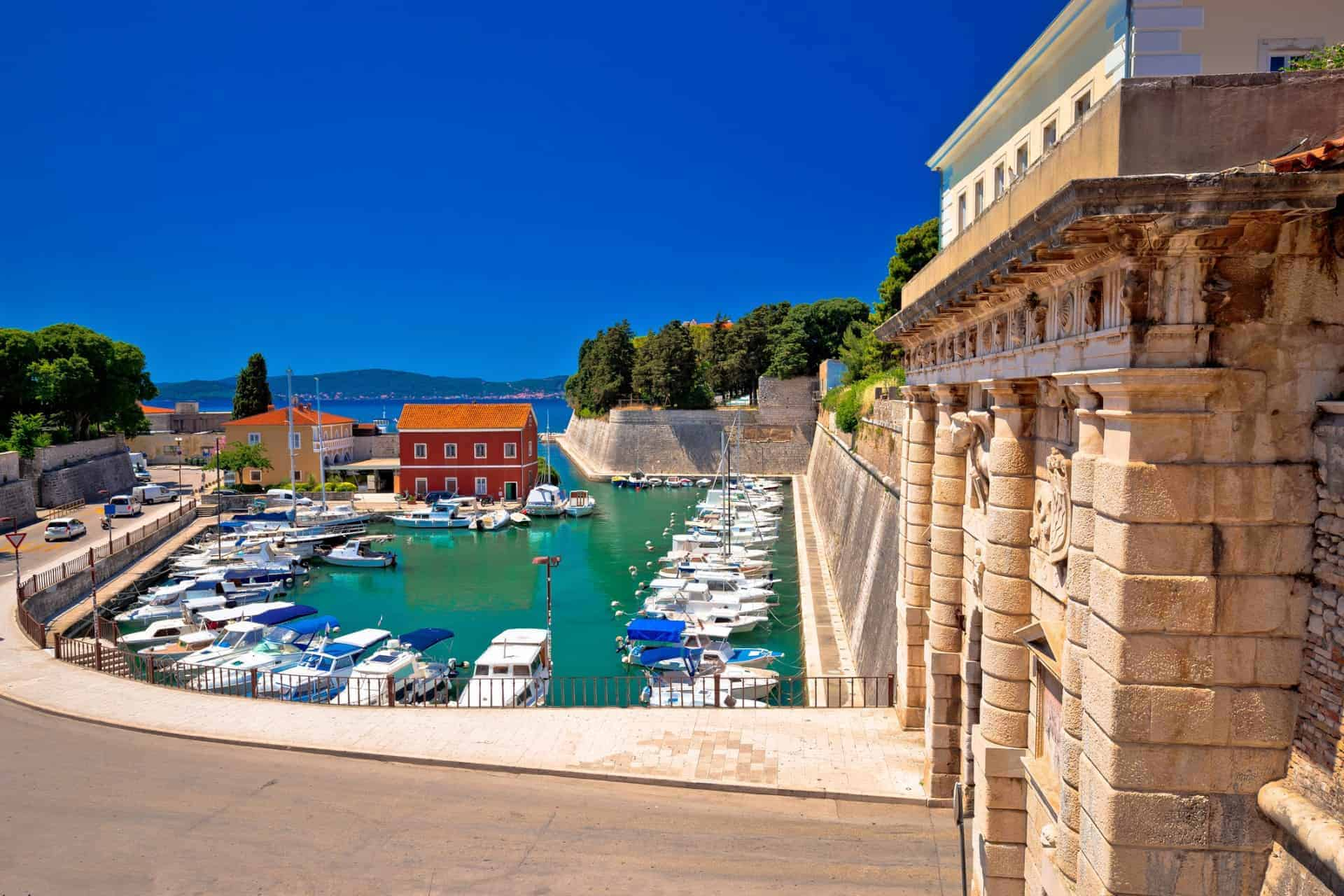 City gate to the walled city of Zadar in Croatia and a view of the harbour