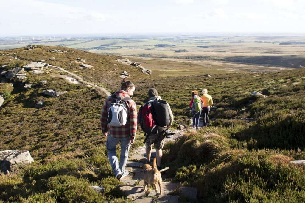 Group of people walking along a stone path in the hills. A pet dog is walking behind them.