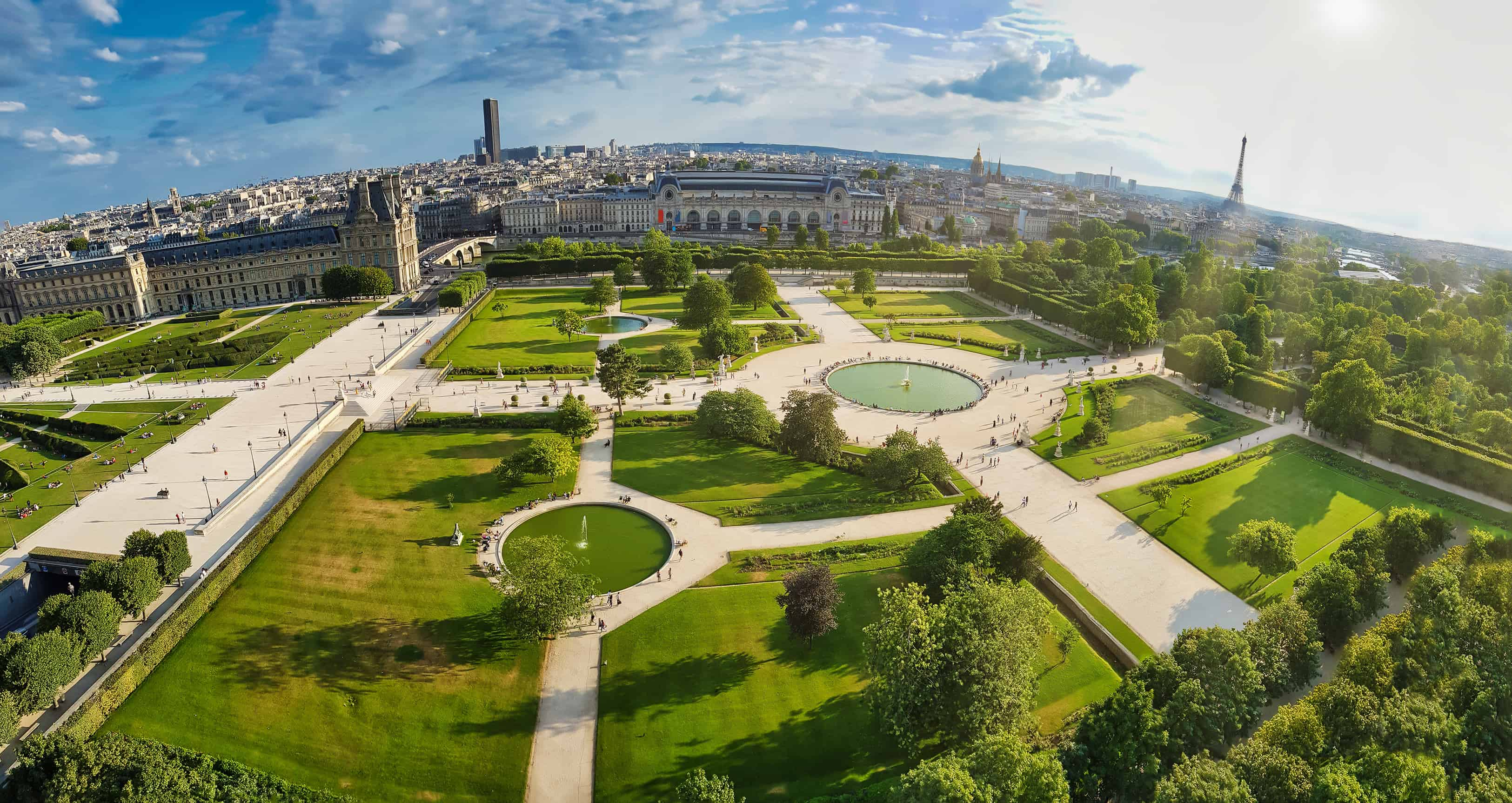 High-angle skyline showing the famous Jardin des Tuileries park of Paris, with the tower of Eiffel in the far horizon.