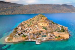 View of the island of Spinalonga with calm sea.
