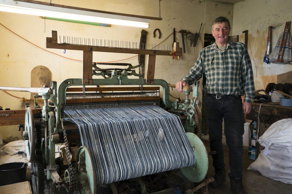 Man beside his Hattersley loom used for creating tweed cloth
